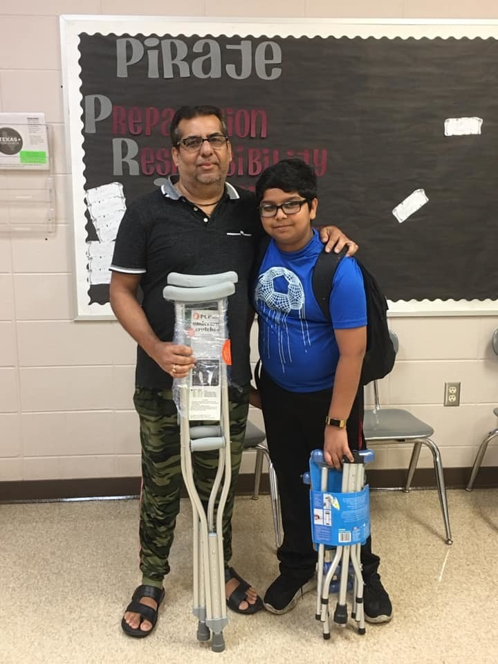 Prince Jeewani and his dad holding medical supplies they're donating